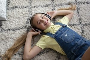 Teenager listening to music lying on carpet